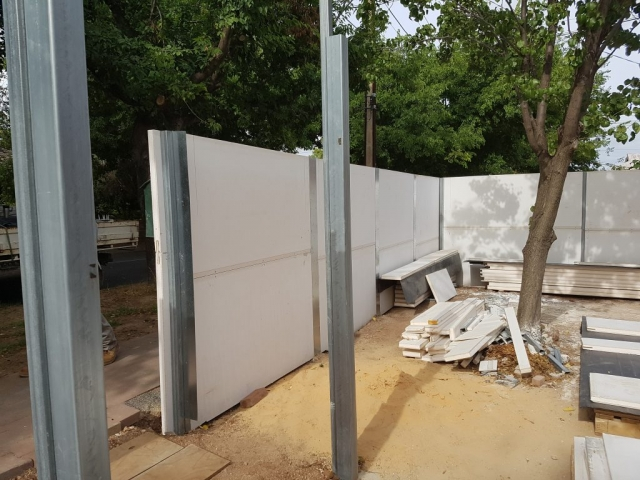 Panels being fitted for an acoustic/privacy fence